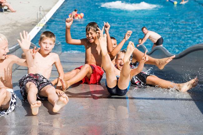 Eine Gruppe Kinder rutscht rückwärts von der Freibadrutsche und lacht