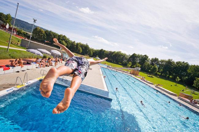 Ein Junge springt vom Sprungbrett