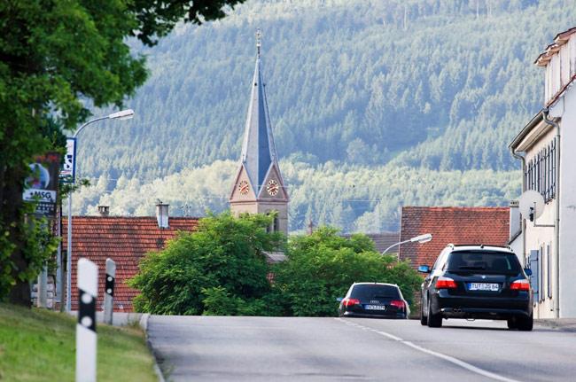 Autos auf einer Spaichinger Straße fahren in Richtung Kirche