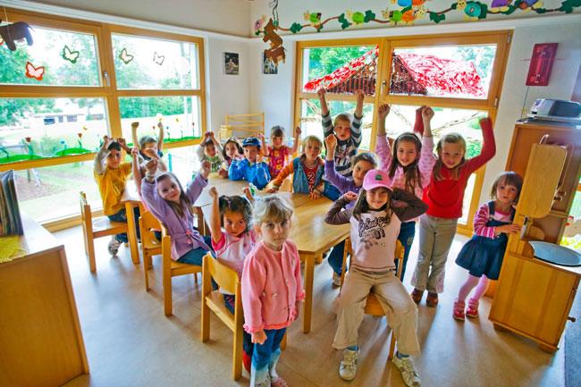 Kindergartenkinder strecken die Arme in die Höhe und freuen sich