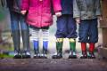 Grundschulkinder in Gummistiefeln stehen auf dem Weg.