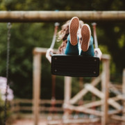 Ein Mädchen schaukelt ausgelassen auf der Holzschaukel