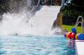Ein Badegast rutscht eine breite Rutsche im Freibad runter.