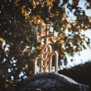 Goldenes Kreuz auf einem Stein im Friedhof