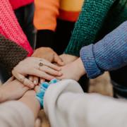 Mehrere Hände übereinander als Symbol für Zusammenhalt