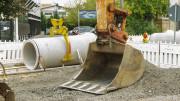 Baggerschaufel auf einer Baustelle und im Hintergrund liegen große Rohre