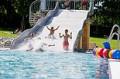 Kinder auf der Wasserrutsche im Freibad