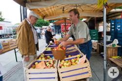 Ein älterer Herr kauft auf dem Wochenmarkt Äpfel
