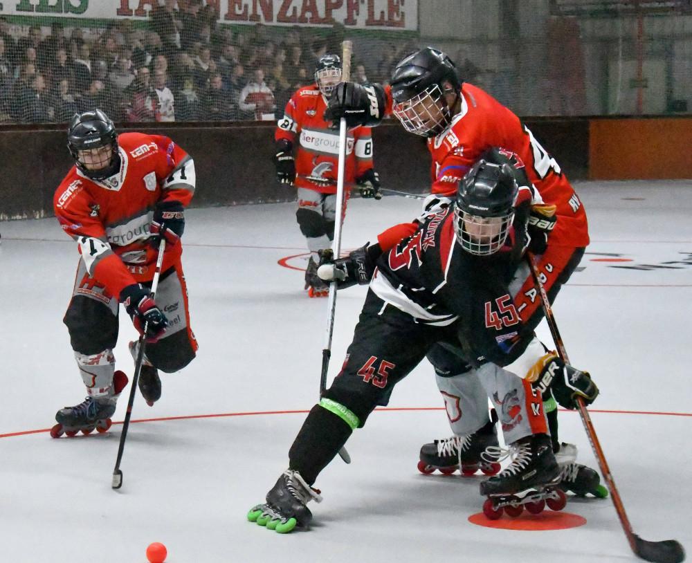 Rollhockeyspieler kämpfen um den Ball